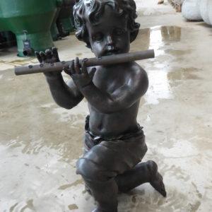 Bruine jongen geknield met fluit